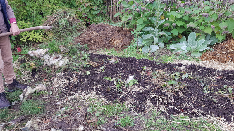 Auf die Holzhäcksel wird die erste Schicht Gartenabfälle aufgetragen