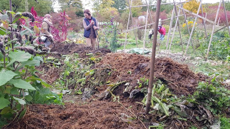 einige Schichten Gartenmaterial, dahinter zwei Gärtnerinnen